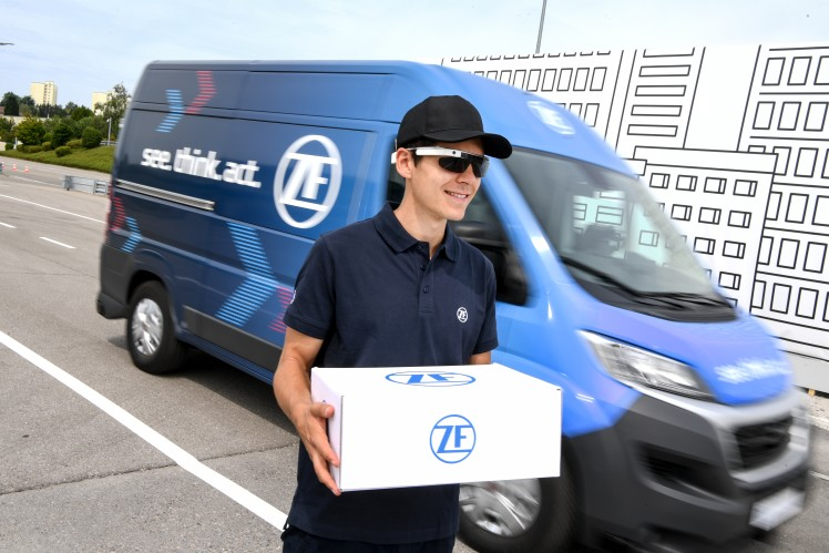 You see a man in front of a moving van. He's holding a package with the ZF logo on it.